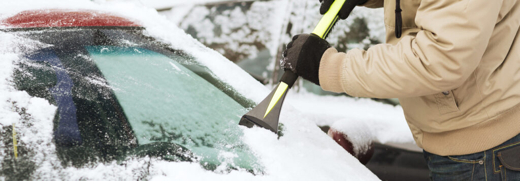 cleaning off a windshield covered in snow